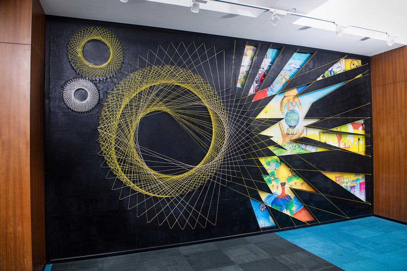 This detailed string art creation at the Tata power wall is a multi-layered artwork that beautifully breaks down the complexity of the journey of energy. The first layer is a print of children's artwork on acrylic sheet which depicts the different sources of energy. On top of that is a charcoal texture painted ply with cutwork, and the top most layer is of string art in dual shades.